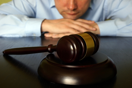 jurors: Justice concept. Man is sitting at the table opposite gavel. Stock Photo