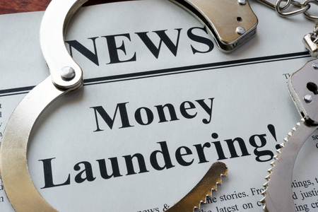 Newspaper with title Money laundering and handcuffs. Stock Photo