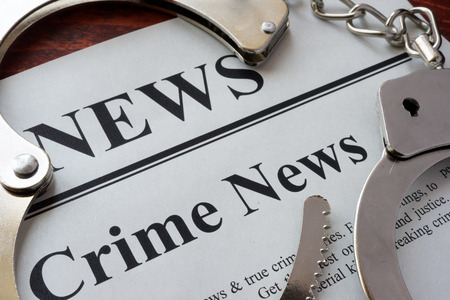 murdering: Newspaper with title crime news and handcuffs. Stock Photo