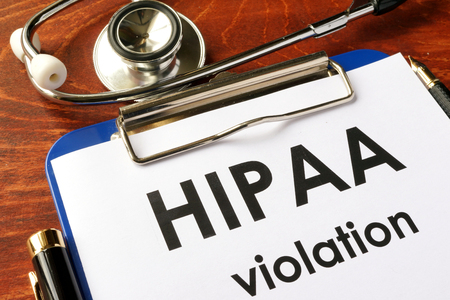 HIPAA violation form on a clipboard. Medical confidentiality concept. Фото со стока