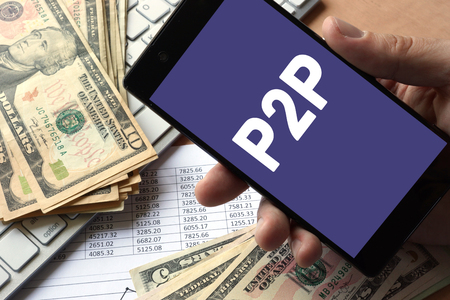 Smartphone in hand with message P2P. Peer to peer lending concept. 스톡 콘텐츠