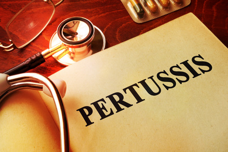 whooping: Book with title Pertussis on a table.