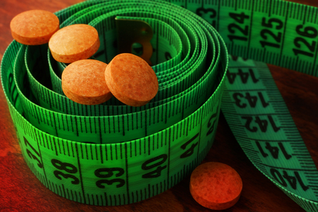 Weight loss supplements on a measuring tape.