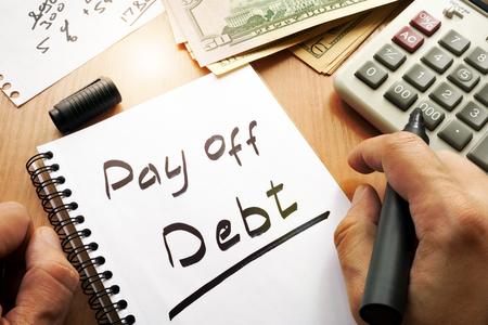 Uwaga ze słowami spłacić koncepcję długów. Zdjęcie Seryjne