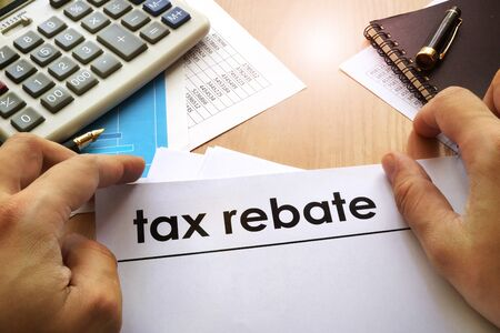 rebates: Hands holding documents with title tax rebate.