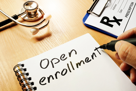 Open enrollment written on a note and medical stethoscope. Stockfoto