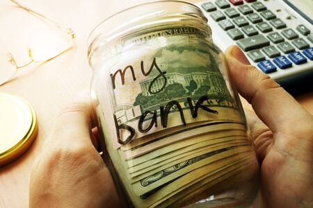 home finances: Jar with dollars and sign my bank on a side. Home finances and savings concept.