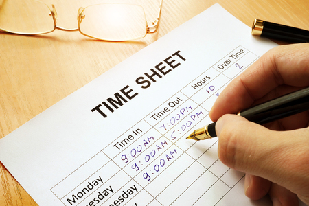 Records work hours in a time sheet. Stockfoto