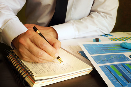 Accounting concept. Manager writing financial data into ledger book.