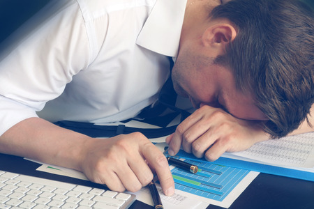 Chronic fatigue syndrome concept. Overworked businessman is sleeping at desk. Stock Photo