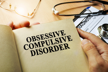 obsessive compulsive: Obsessive compulsive disorder concept. Book on a tablr.