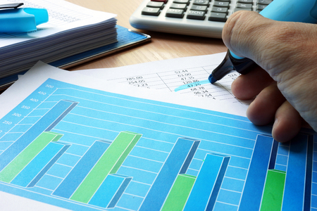 Auditor is underlined financial data in a business report. Фото со стока