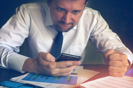 Angry businessman reading message in a smartphone. Problems in a business.