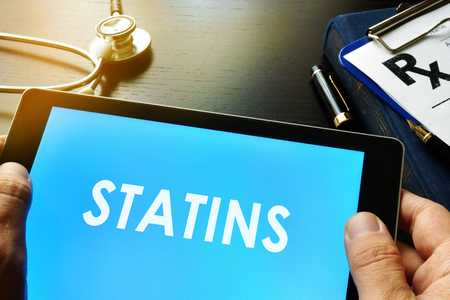Doctor holding a tablet with word statins.