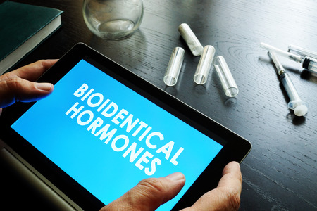 Bioidentical hormones. Doctor holding tablet with sign.