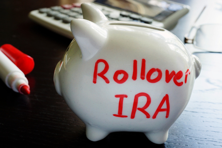 Rollover IRA written on a piggy bank. Stock Photo - 87588428
