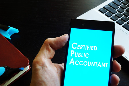 Hand holding phone with sign Certified public accountant (CPA). Stock Photo