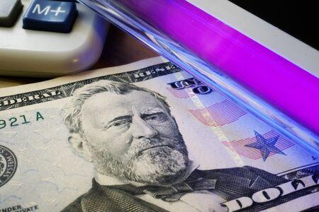 Checking dollar banknotes in a UV light. Counterfeit money concept.