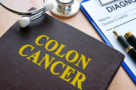 Book with title colon cancer and stethoscope.