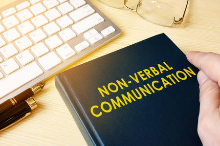 Book about NVC Non-verbal communication on a table. Archivio Fotografico