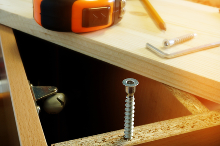 Furniture assembling. Parts of cabinet and screw close up. Stok Fotoğraf - 93211428