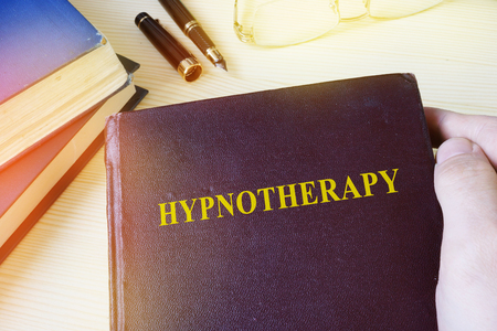 Man holding book with title Hypnotherapy.