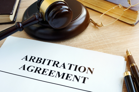 Arbitration agreement resolution of commercial disputes on a desk.