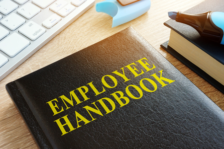 Employee handbook on a wooden desk. 스톡 콘텐츠