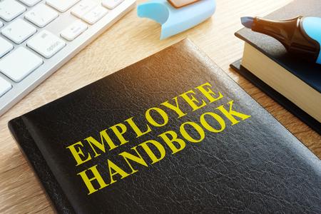 Employee handbook on a wooden desk. Foto de archivo