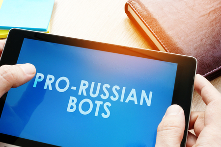 Man holding tablet with words pro-russian bots. Russian internet propaganda concept.