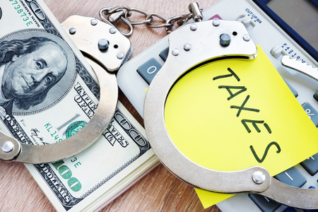 Problems with taxes. Handcuffs and money. Tax evasion concept.