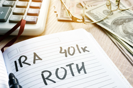 Words IRA 401k ROTH handwritten in a note. Retirement plans.