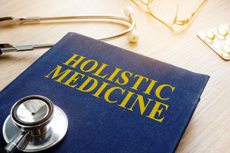 Book about holistic medicine and stethoscope. Stock Photo