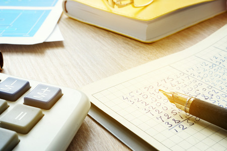 Accountant workplace with calculator, accounting documents and ledger book.