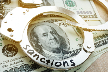 Word sanctions on a handcuffs and American dollar bills. Economical restrictive measures. Stockfoto