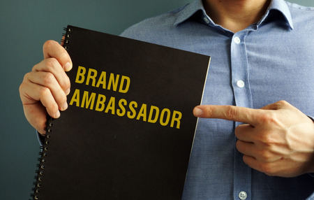 Man is holding book with title Brand Ambassador. Foto de archivo