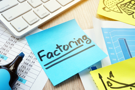 Stick with word factoring on a desk. Factor concept.
