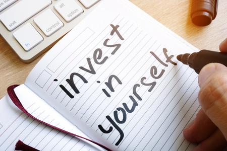 De mens schrijft investeer in jezelf in een notitie.