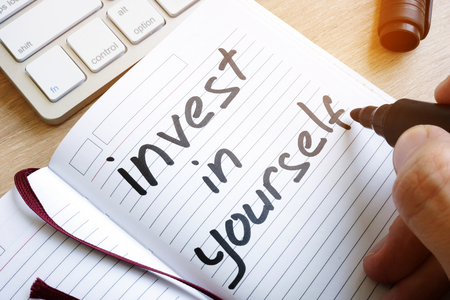 Man is writing invest in yourself in a note. Foto de archivo