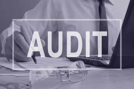Audit concept. Auditor is working with ledger.