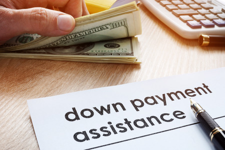 Down payment assistance form and dollar banknotes. Archivio Fotografico