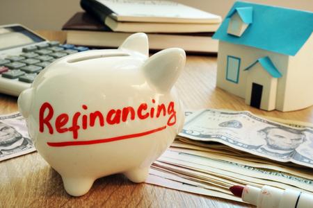Refinanzierung auf einem Sparschwein geschrieben. Standard-Bild