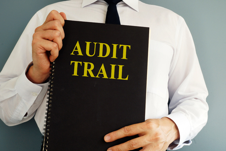 Audit trail concept. Auditor holding book.