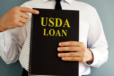 USDA Loan concept. Man holding book. Stock fotó - 102811653