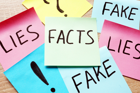Memo sticks with words Facts, lies and fakes. Modern news concept.