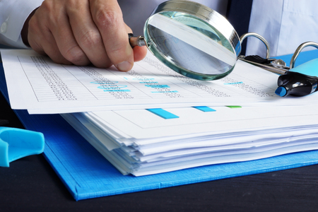 Il revisore sta lavorando con i documenti finanziari. Audit o valutazioni. Archivio Fotografico