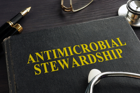 Book about Antimicrobial stewardship (AMS) and stethoscope. Standard-Bild