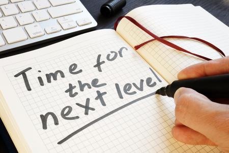 El hombre está escribiendo tiempo para el siguiente nivel. Motivación.