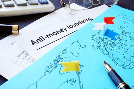 Anti-Money Laundering (AML) documents and world map. Stock Photo