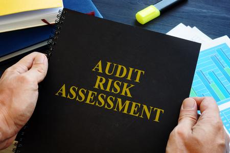 Man is holding Audit risk assessment report.